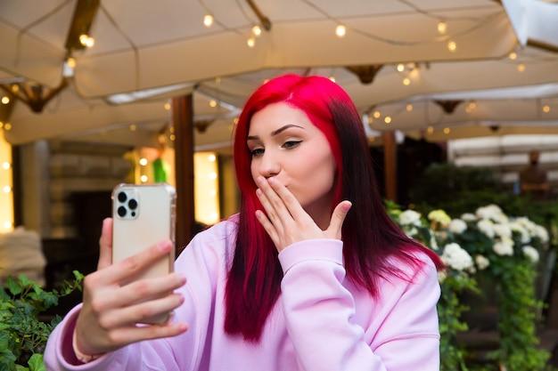 카페에 있는 아름다운 빨간 머리 인플루언서 블로거 소녀는 소셜 네트워크에서 구독자와 스마트폰으로 화상 통화를 하고 있습니다.