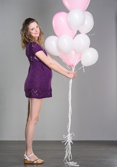 風船とドレスの美しい赤毛の妊婦