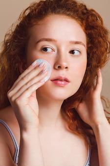 아름 다운 red-haired 십 대 소녀는 면봉으로 그녀의 피부를 정화합니다.