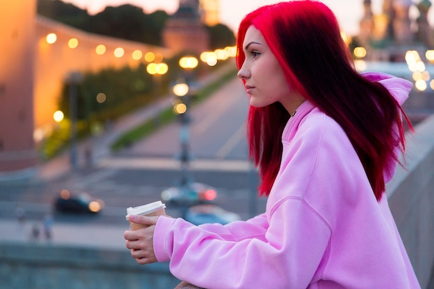 明るい街の通りで夕方にコーヒーを飲むピンクのパーカーの美しい赤毛の10代の少女。