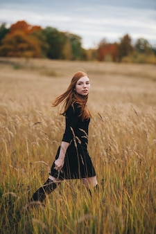 Beautiful red-haired woman in a black dress walks on an autumn field.