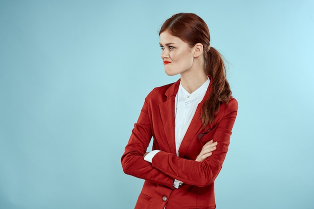 Beautiful red-haired woman in a business suit and red hat, stylish office image
