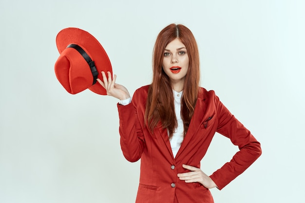 Beautiful red-haired woman in a business suit and red hat
