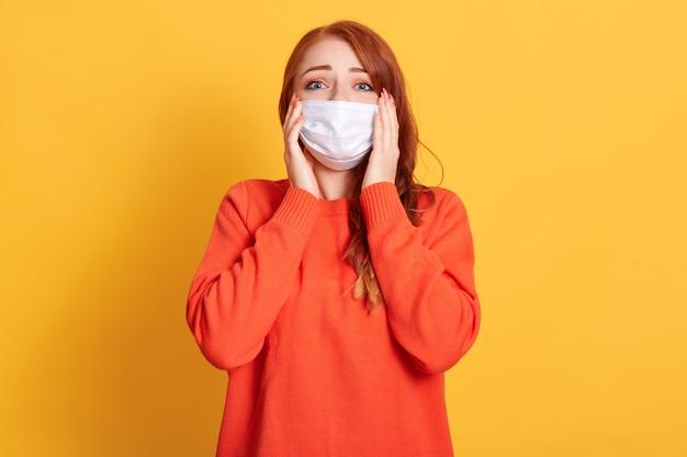 美しい赤い髪の女性は彼女の頭にしがみついて、コロナウイルスの広がりによってショックを受けています。黄色のスペースに防護マスクの赤い髪の少女