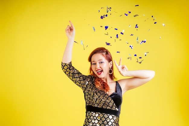 Beautiful red-haired woman dancing dance in yellow background in studio