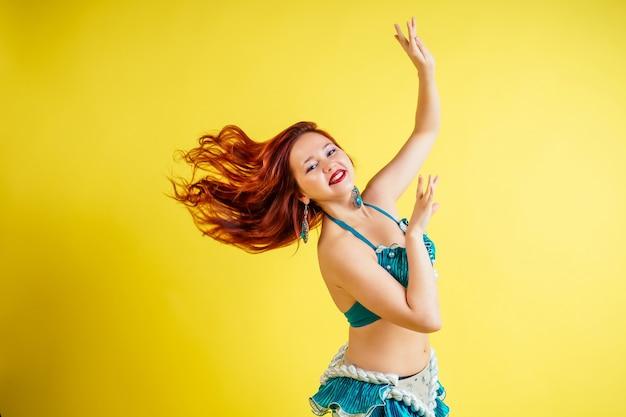 スタジオで黄色の背景に青いスーツで東洋のベリーダンスを踊る美しい赤毛の女性。