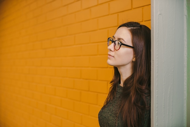 Beautiful red-haired woman in glasses on yellow brick wall