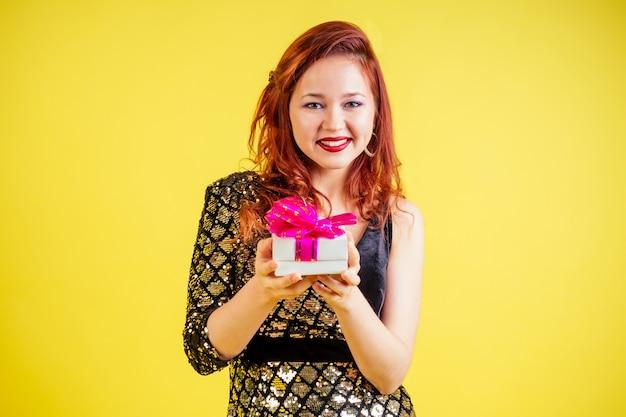 スタジオで黄色の背景にギフトボックスを保持している美しい赤髪の女性