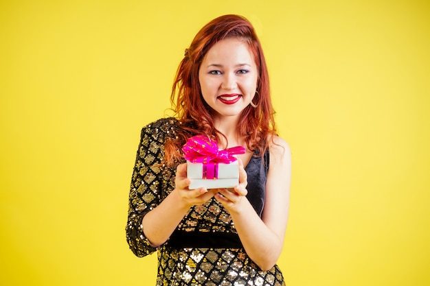 Beautiful red-haired woman holding gift box in yellow background in studio