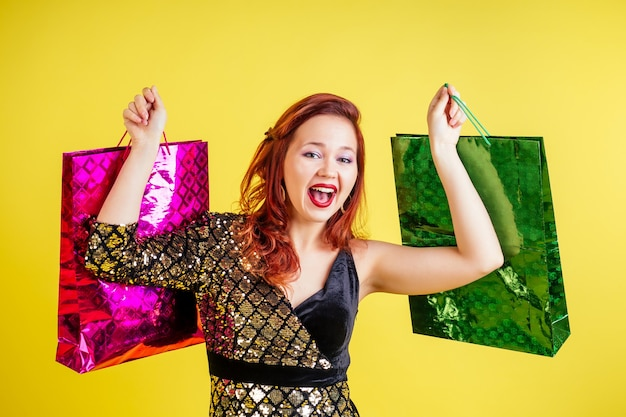 Beautiful red-haired woman holding shopping bags in yellow background in studio