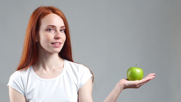 Beautiful red-haired woman holds a green apple in her palm