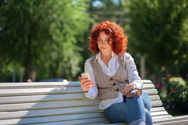 Красивая рыжая женщина летом сидит на скамейке в парке и пользуется телефоном