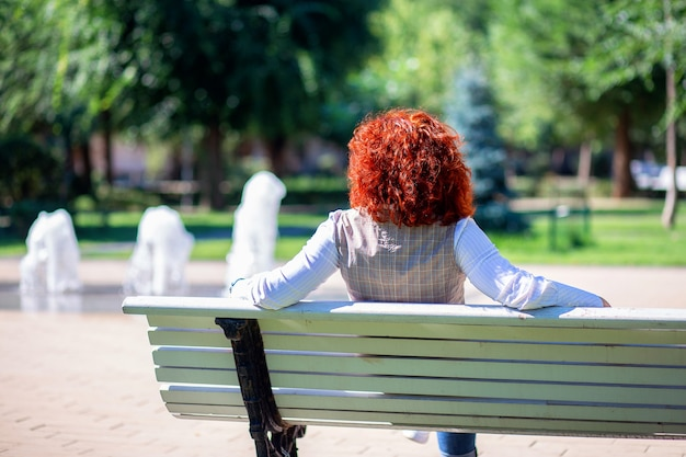 Красивая рыжая женщина сидит в парке на скамейке