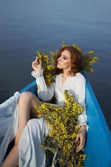 아름 다운 빨간 머리 여자는 그녀의 손에 꽃과 함께 보트에 놓여 있습니다. 호수에 나무 보트에 긴 흰색 드레스에 아름다움 로맨틱 초상화 소녀