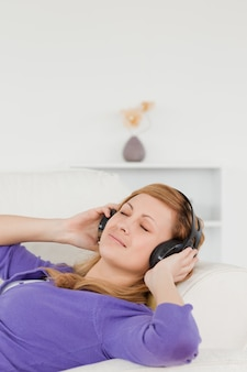 Beautiful red-haired woman listening to music while taking a rest while lying on a sofa