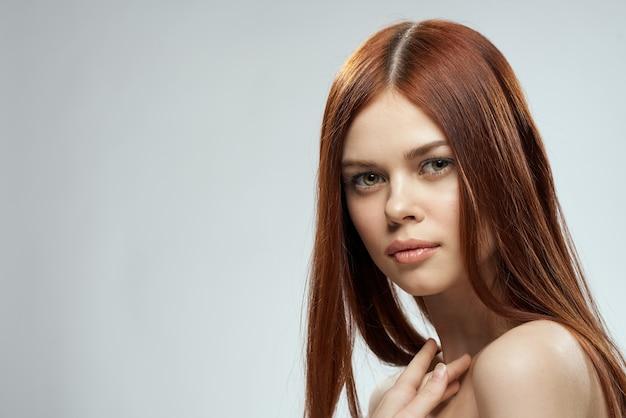 美しい赤毛の女性の裸の肩の化粧品の長い髪