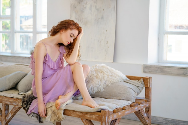 Beautiful red-haired woman sitting in the studio in a sad mood.