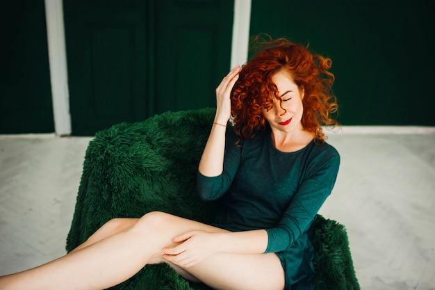 Beautiful red-haired woman sitts on a green armchair