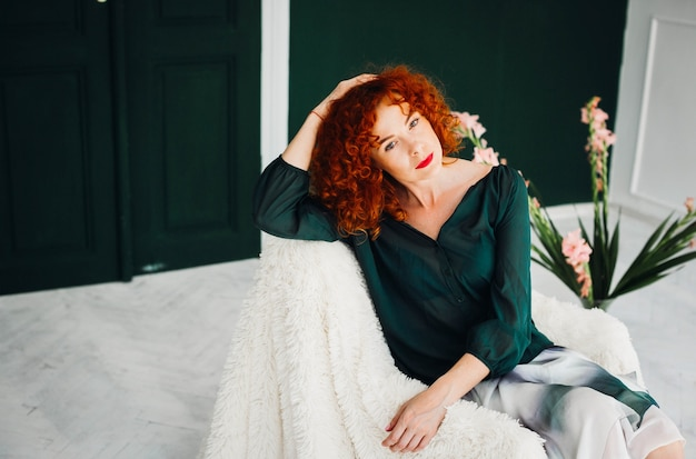 Beautiful red-haired woman sitts on a white armchair