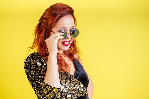 Beautiful red-haired woman in sunglasses dancing dance in yellow background in studio