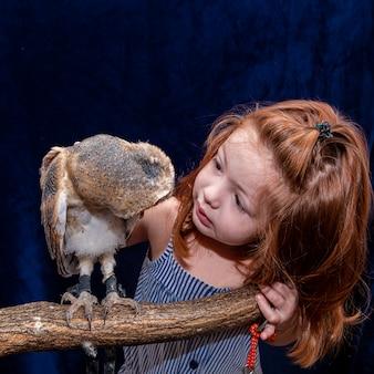 ペットのフクロウと一緒に写真を撮る美しい赤髪の女