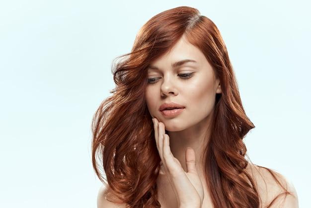 巻き毛を持つ美しい赤髪の女。枝毛のない、健康的で光沢のあるヘアケア