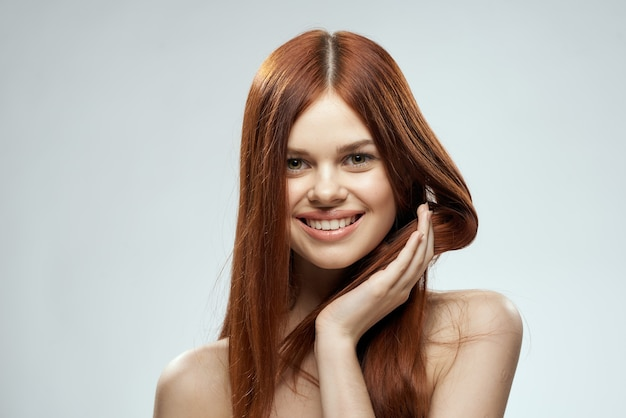 Beautiful red-haired woman with naked shoulders and long hair glamor light background.