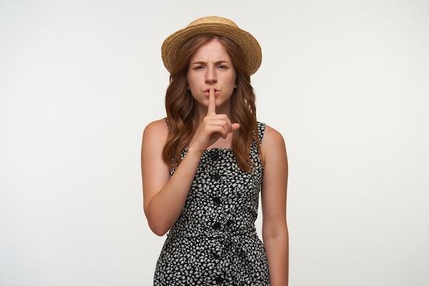 Bella giovane femmina dai capelli rossi in abito bianco e nero che guarda con l'indice alzato alla bocca, facendo gesto di silenzio