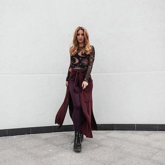 보라색 케이프와 부츠에서 바지 패턴의 유행 블라우스에 아름 다운 빨간 머리 젊은 여자가 배경에 간다