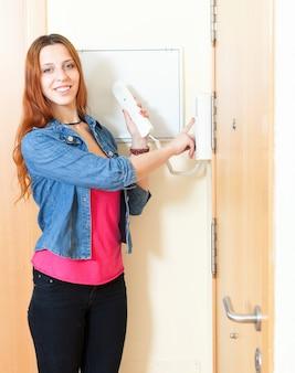 Красивая рыжая молодая женщина разговаривает по дому видеофон