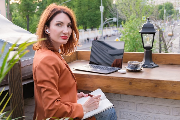 노트북, 커피 한 잔, 무선 헤드폰을 가진 아름다운 빨간 머리 젊은 여성이 카페의 열린 베란다에 앉아 있습니다. 여자는 노트북에 메모를 합니다. 온라인 교육.