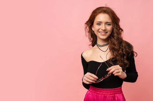 분홍색 벽에 포즈를 취하는 아름 다운 빨간 머리 여자. 물결 모양의 머리카락. 완벽한 미소.