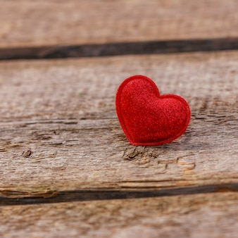 A beautiful red heart lies on a wooden background