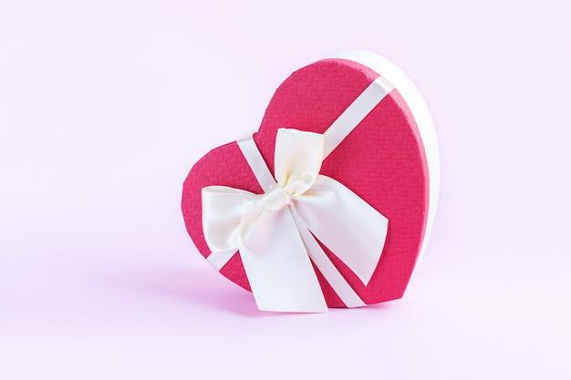 밝은 분홍색 배경에 리본 활이 있는 아름다운 붉은 하트 모양의 선물 상자
