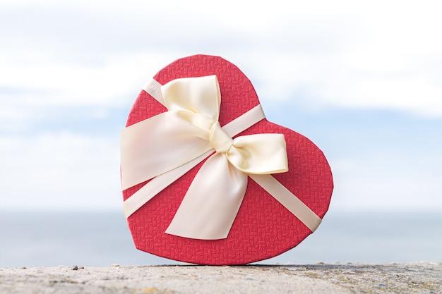 야외에서 리본 활이 있는 아름다운 붉은 심장 모양의 선물 상자