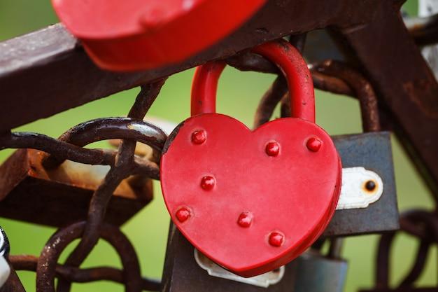 Beautiful red heart-shaped padlock locked on iron chain