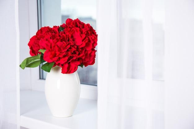 窓枠の花瓶に美しい赤いアジサイの花