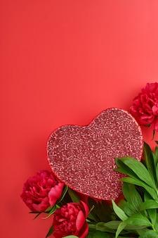 Красивый красный букет цветов пиона с красной подарочной коробкой на красном фоне, вид сверху, копия пространства, плоская планировка. день святого валентина, день матери фон.