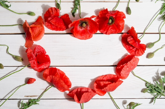 Beautiful red poppies in shape of heart on wooden background