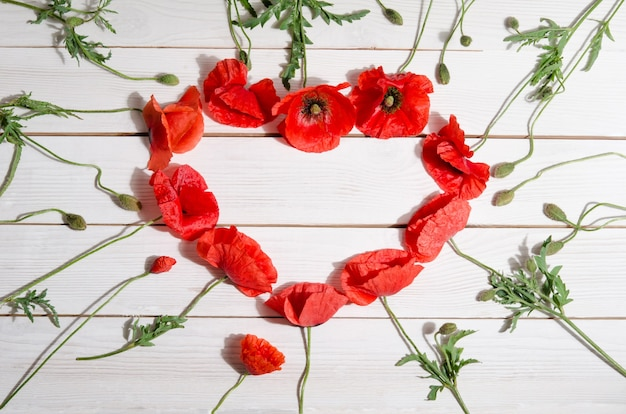 Beautiful red poppies in shape of heart on wooden surface