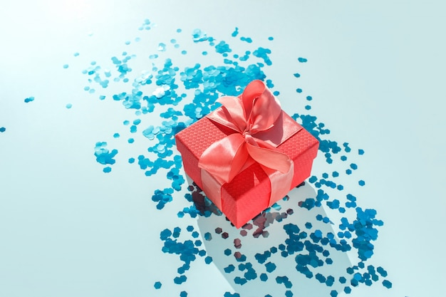 Beautiful red present box tied up with shiny satin coral ribbon on turquoise