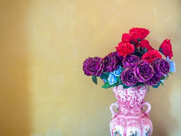 Красивые красные, фиолетовые и синие цветы в винтажной керамической вазе на желтой стене с копией пространства.