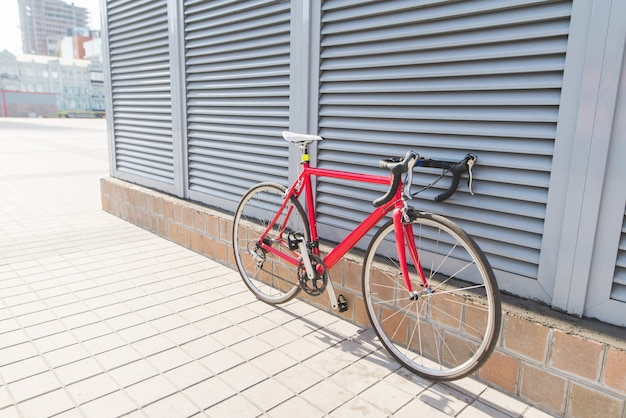 Beautiful red road bike stands near a gray wall