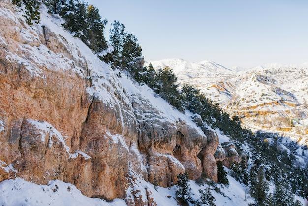ウズベキスタンのベルダーセイリゾートのエリアで雪に覆われた美しい赤い岩の山の斜面