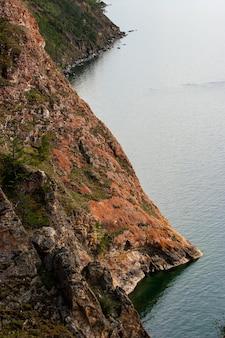 Красивые красные скалы на берегу байкала на острове ольхон. вертикальная рамка. крутые скалы уходят в воду.
