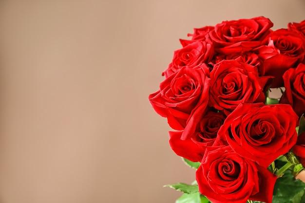 色の表面に美しい赤いバラ