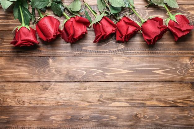 木製の背景に美しい赤いバラ