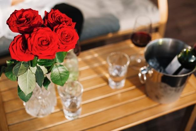 나무 테이블에 아름 다운 빨간 장미 꽃병