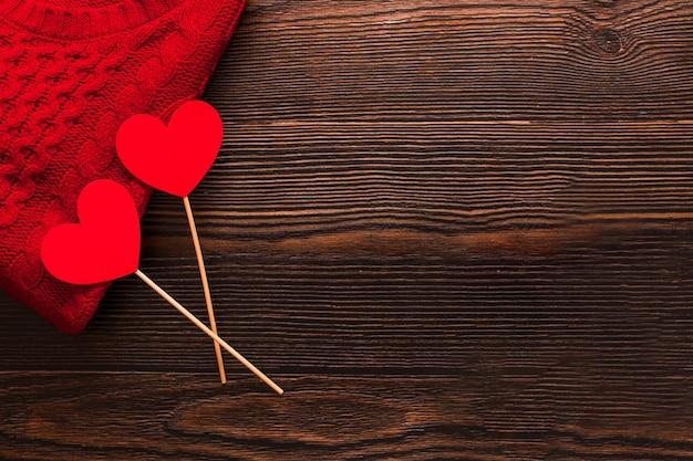 아름 다운 빨간 스웨터와 어두운 나무 배경에 고립 된 막대기에 두 개의 빨간 하트. flatlay의 윗면보기. 발렌타인과 크리스마스 개념입니다. copyspace, 패션.