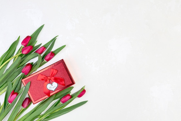 Beautiful red tulips and gift box on a textured white background with a copy of the space